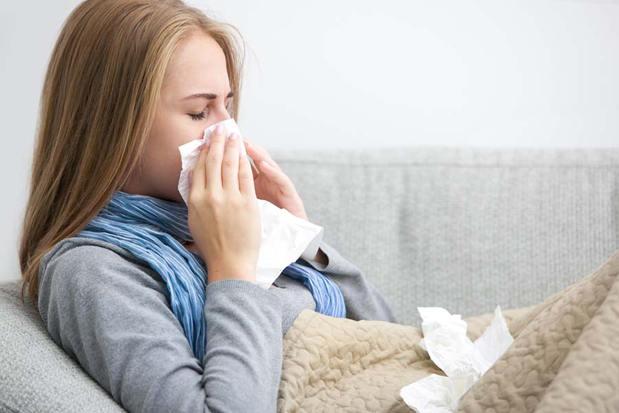Close up of a young woman sneezing into a tissue.