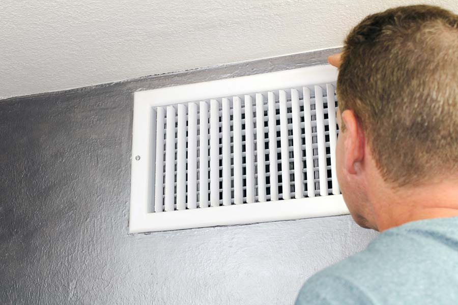 Mature male peering inside an upper wall white grid air duct on a silver wall near a white ceiling. A guy inspecting a heating and cooling air register duct for maintenance.