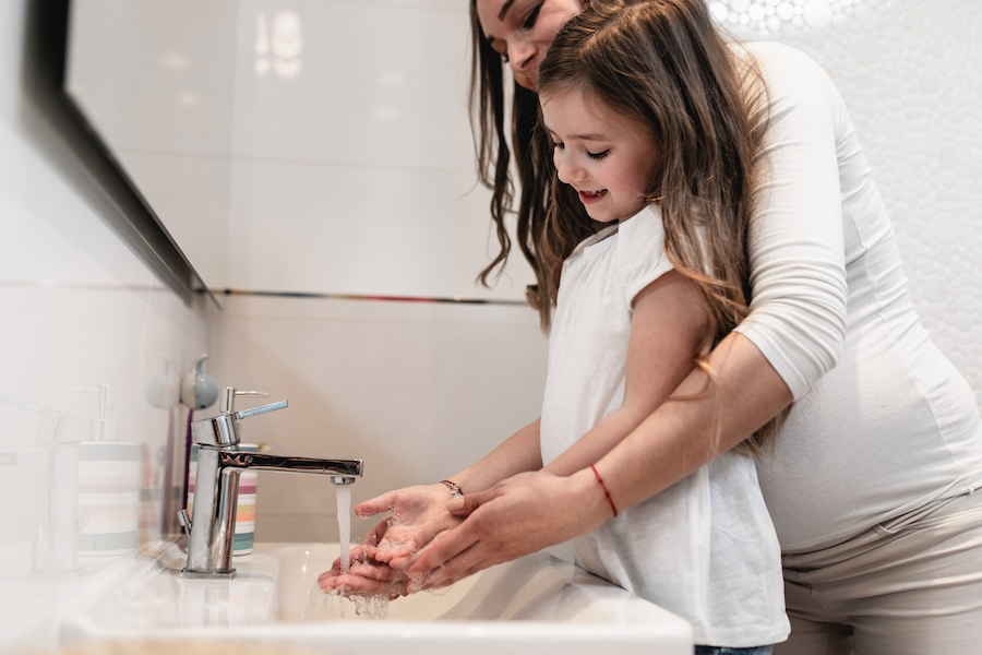 Kid washing hands at home as part of the HVAC FAQ for COVID-19.