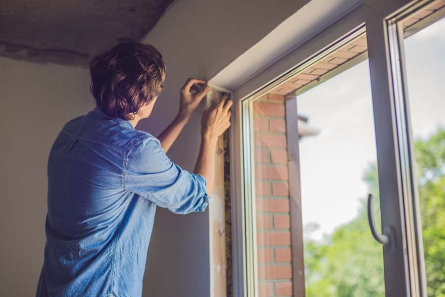 Man checking window insulation as part of the heat gain prevention tips.