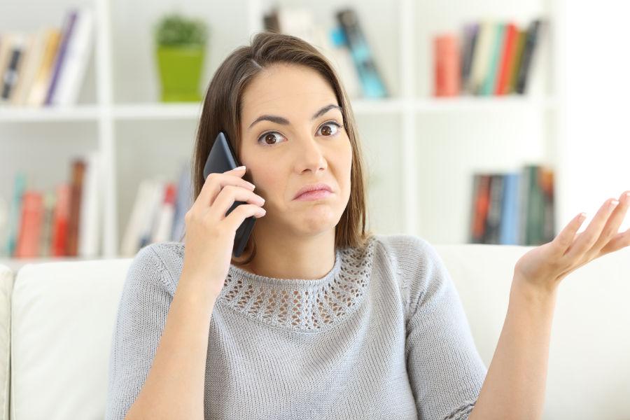woman on phone with HVAC company asking if you really need an AC tune-up.