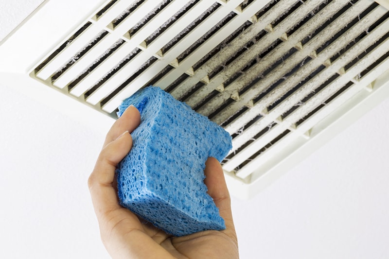 Close up horizontal photo of female hand cleaning dirty bathroom fan vent cover with blue sponge, why air duct cleaning is important